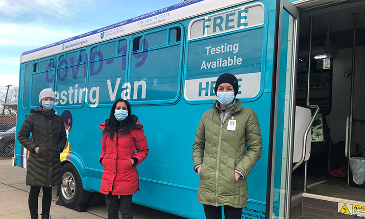 Three people standing in front of COVID-19 testing van