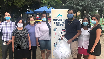 Team with bag of COVID-19 care kits